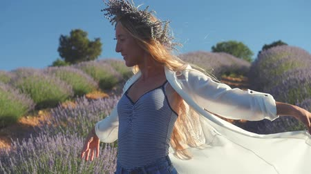 loira : Young woman in lavender wreath standing gorgeously in lavender field in windy weather. Raising hands holding shirt in slow motion Stock Footage