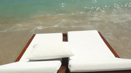 vacant : Front view of luxury white sunbeds by the stormy turquoise sea. Summer vacation concept.
