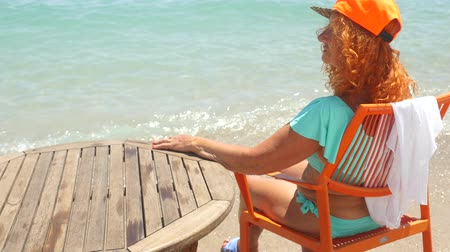anlamı : Youthful 78 years old woman enjoying her life sitting in blue bikini and orange cap by the sea