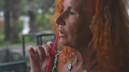 nobreza : Attractive red haired 78 years old woman drinking using tubule at cafe, outdoors. Grandmother at date. Vídeos