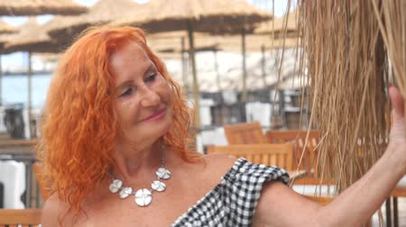 Attractive red haired 78 years old woman relaxing at summer resort. Enjoying her vacation.