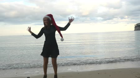 lelkesedés : Christmas and holiday concept. Funny woman in Santa hat having fun over sea background Stock mozgókép