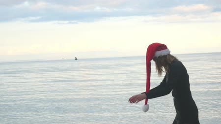 Lonely Christmas and holiday concept. Woman in Santa hat sadly walking over sea background. Stock mozgókép