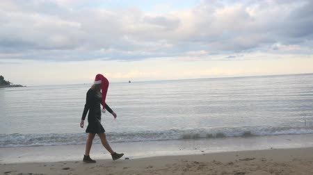 bizarre : Lonely Christmas and holiday concept. Woman in Santa hat sadly walking over sea background. Stock Footage