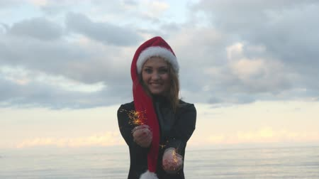 Young pretty woman in Santa hat and in black dress happily holding sparklers on sea background