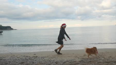 Young woman running after funny Pomeranian Spitz near the sea. Both in Santa hats. New Year holiday concept.