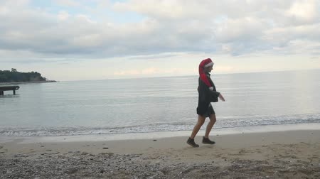 Young woman and funny Pomeranian Spitz in Santa hats running by the sea. New Year holiday concept.