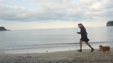 Young woman and funny Pomeranian Spitz in Santa hats running by the sea. New Year holiday concept. Slow motion