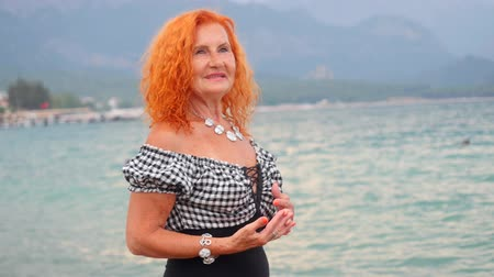 Attractive red haired 78 years old woman standing by the sea and enjoying mountain views. Happy at summer resort. Stock mozgókép