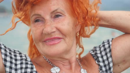 Portrait of attractive red haired 78 years old woman standing by the sea and enjoying the nature. Happy at summer resort. Stock mozgókép