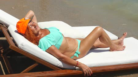 Youthful 78 years old woman enjoying her life sitting in blue bikini and orange cap by the sea. Sunbathing just near the sea.