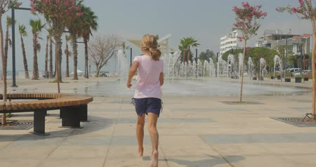 Young girl in shorts and t-shirt running fast in city park of southern country towards the fountain