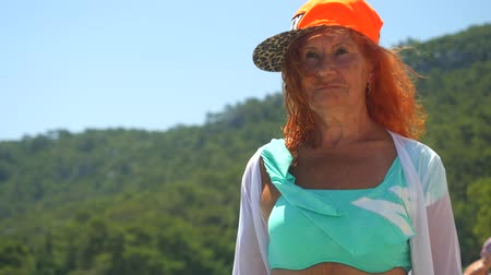 anlamı : Youthful 78 years old woman enjoying her life walking in blue bikini and orange cap by the sea. Summer vacation concept. Stok Video