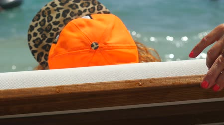 nobreza : Backside view of youthful old woman lying on the sunbed. Orange cap and hands with bright manicure. Sunbathing by the sea. Vídeos