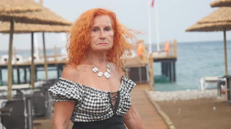 Attractive red haired 78 years old woman walking towards the sea then turning and looking at camera. Relaxing at summer resort. Enjoying her vacation near the sea.