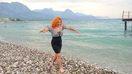 Attractive red haired 78 years old woman funny walking on the stone beach. Happy at summer resort.