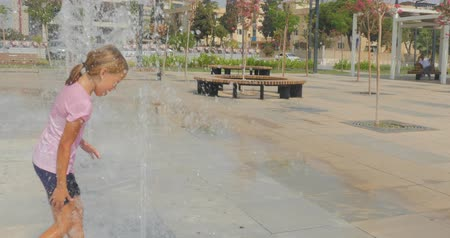 Young girl in wet shorts and t-shirt having fun in city park fountain in southern country