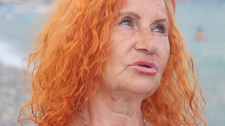 Portrait of attractive red haired 78 years old woman standing by the sea. Different artistic emotions.