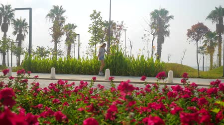 Teenage girl in roller-skates skating on the beautiful city park road with palms and red flowers. Slow motion