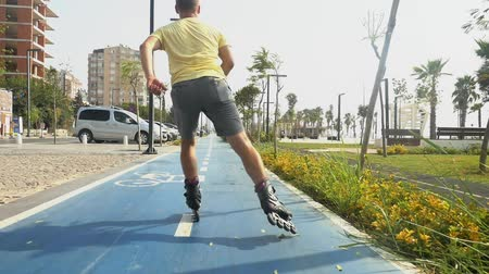 Young sporty man roller skating in summer city park in slow motion