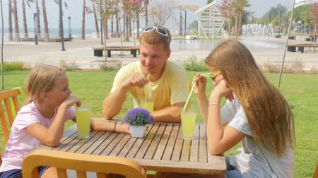 Family of father and two sisters chatting and drinking lemonade outdoors in summer cafe