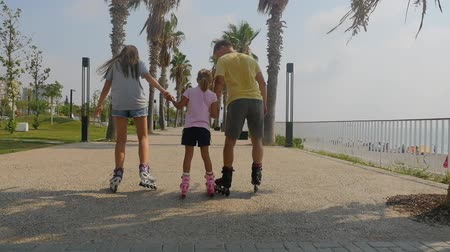 Father with daughters roller skating on rink. Backside view in movement. Beautiful summer park.