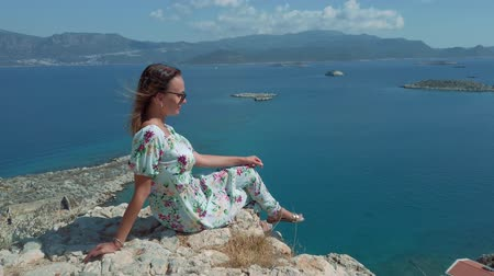 Young woman in summer dress sitting on the edge of cliff above Mediterranean sea in Kastelorizo, Meis Greek island