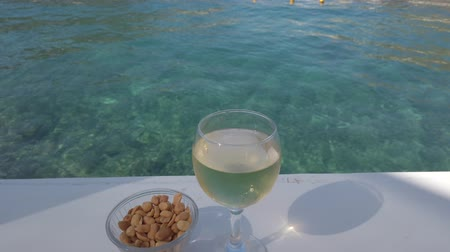 prestiž : Closeup of glass of white wine with nuts in a cup on the table near the turquoise sea