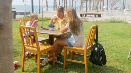 восхитительный : Family of father and two sisters chatting and drinking lemonade outdoors in summer cafe