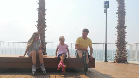 Father with daughters sitting on the bench in roller skates. Having fun over sea background