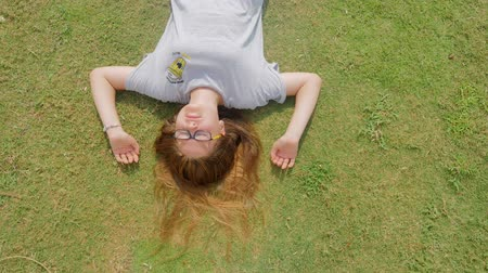 tienermeisje : Teenage girl wearing glasses falls on the green grass and rolls aside Stockvideo
