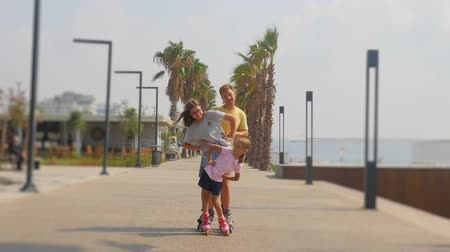 teen age : Father with daughters roller skaters happily posing. Beautiful summer park with palms and sea view. Stock Footage