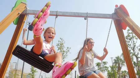 álmodozó : Sisters swinging together on playground. Summer time, southern country, having fun
