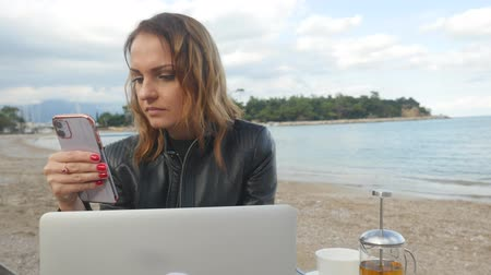 Business woman working in the outdoor cafe using laptop and mobile phone Stok Video