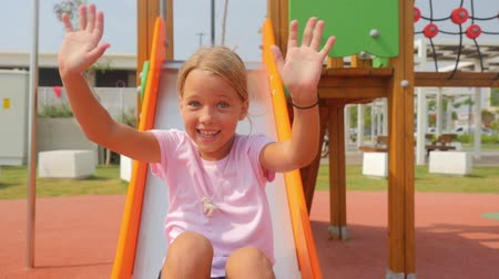Girl sliding down on playground and waves her hands in slow motion. Summertime Stok Video
