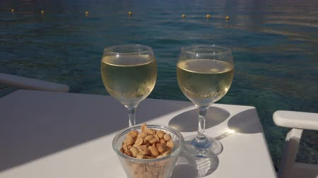 prestiž : Closeup of two glasses of white wine with nuts in a cup on the table near the turquoise sea