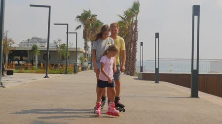 Father with daughters roller skaters happily posing then moving in different sides. Beautiful summer park with palms and sea view.
