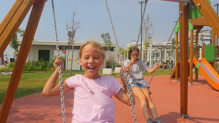 Sisters swinging together on playground. Summer time, southern country, having fun