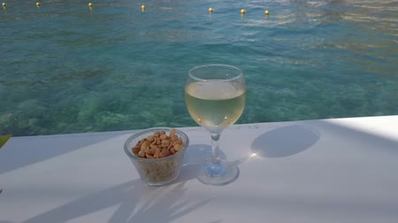 idílio : Closeup of glass of white wine with nuts in a cup on the table near the turquoise sea