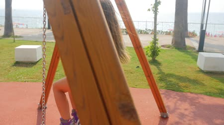 álmodozó : Teenage girl spins on the swing in slow motion. Summer time, southern country Stock mozgókép