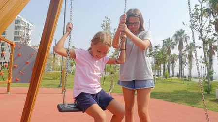 Sisters swinging wearing roller skates in slow motion. Summer time, southern country, having fun