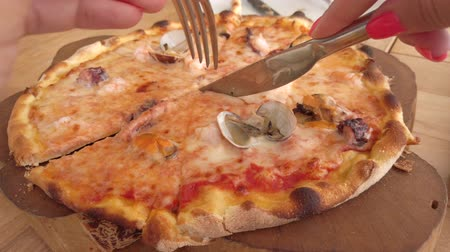 cheese slice : Freshly baked thin crust seafood pizza being sliced with melty cheesy closeup