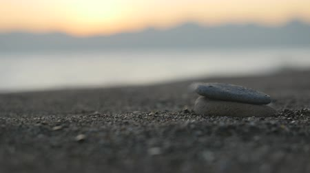 shui : Closeup of childs hand making pebble tower on beach at sunset time. Soul harmony concept Stock Footage