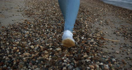 отдыха : Female feet in shoes walk on small stones by the sea