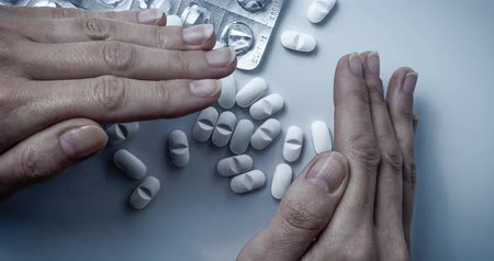 addiction recovery : Hands covers and hiding many white prescription drugs, medicine tablets or vitamin pills in a pile - Concept of healthcare, opioids addiction, shame, medicament abuse or medication treatment