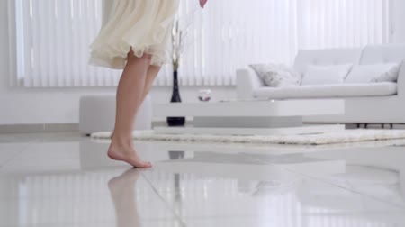 step : Beautiful young girl bare feet moving on interior in the living room in slow motion. View of young girl elegantly to walk.Sexy legs. Floor. Gait.