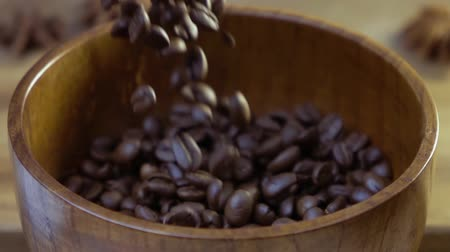 sifted : Coffee beans fall into a wooden dish. Slow motion.