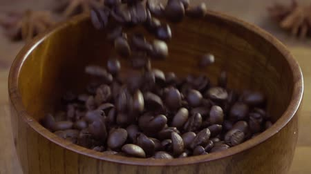 sifted : The coffee beans fall on the table in a wooden dish. The gray background. The fall and flight of seeds video