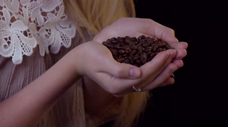 saborear : Smelling coffee beans - a young woman cups them in her hands