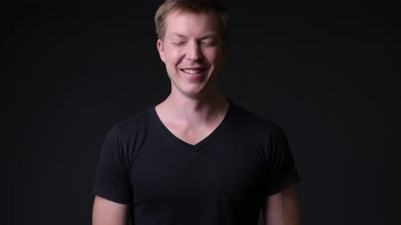 finnish : Young handsome man against black background